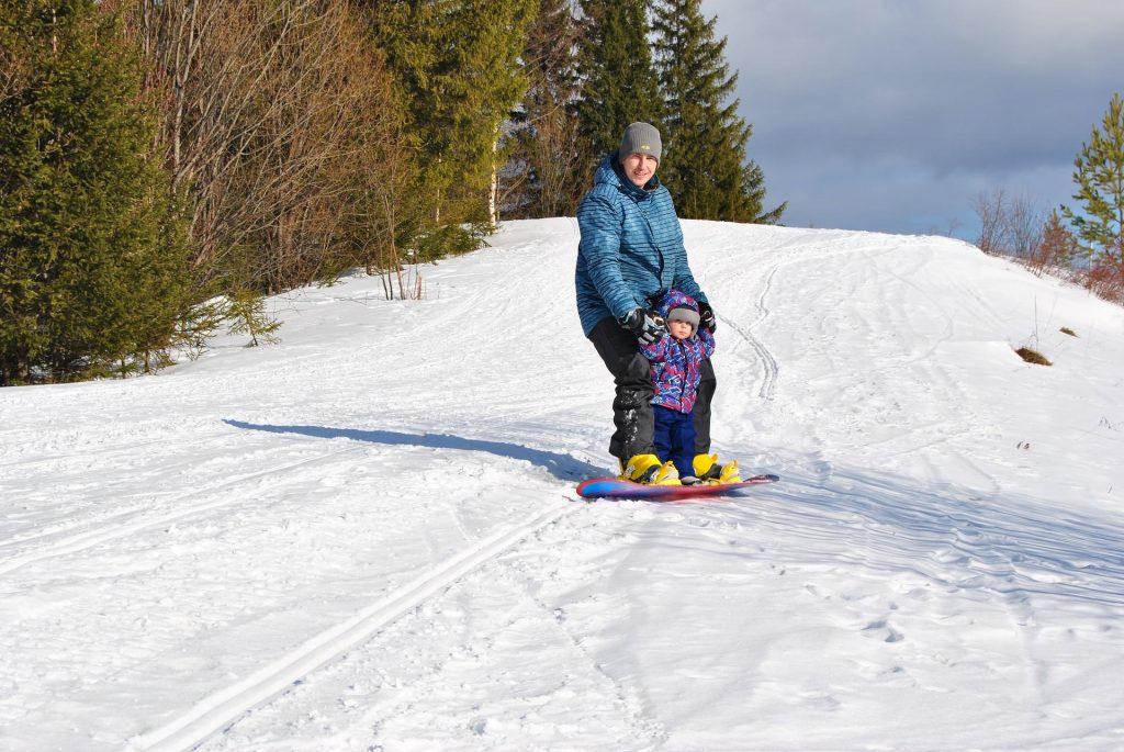 niño practicando snowboarding con adulto